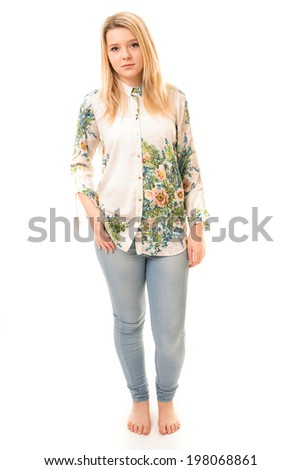 Portrait of a beautiful blond teenage girl wearing blue trousers, a flowery white shirt and bare feet isolated against a white background - stock photo