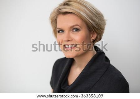 Portrait of a beautiful blond woman in an elegant dress - stock photo