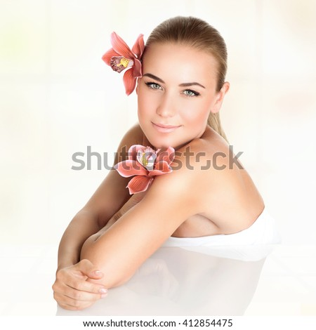 Portrait of a beautiful blond woman with orchid flowers, spending day at spa salon, relaxation during medical beauty treatments, skin care - stock photo