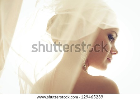 Portrait of a beautiful blonde bride. Wedding day. Daylight. Indoor shot