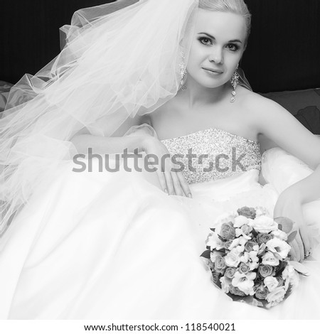 portrait of a beautiful blonde bride with great vapory veil and  wedding bouquet - stock photo