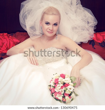 Portrait of a beautiful blonde bride with great vapory veil and wedding bouquet. Indoor shot