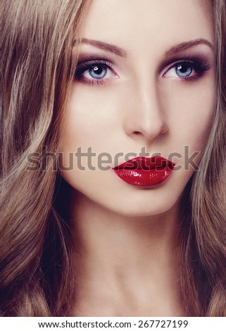 Portrait of a beautiful blonde fashion model face with red lips