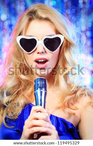 Portrait of a beautiful blonde girl singing with a microphone.