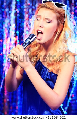 Portrait of a beautiful blonde girl singing with a microphone. Disco lights in the background.