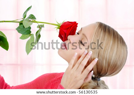 Portrait of a beautiful blonde girl sniffs a red rose