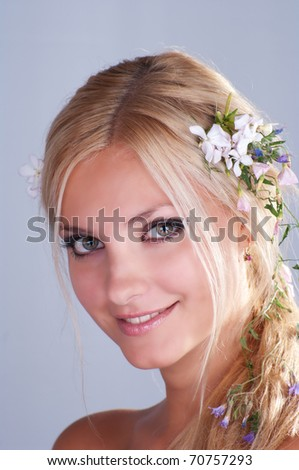 Portrait of a beautiful blonde girl with flowers in her hair - stock photo