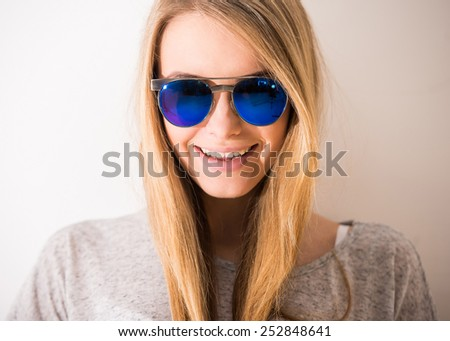 Portrait of a beautiful blonde girl with sunglasses is smiling. - stock photo