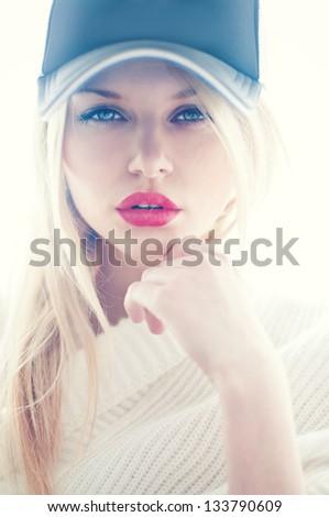 portrait of a beautiful blonde in a cap - stock photo