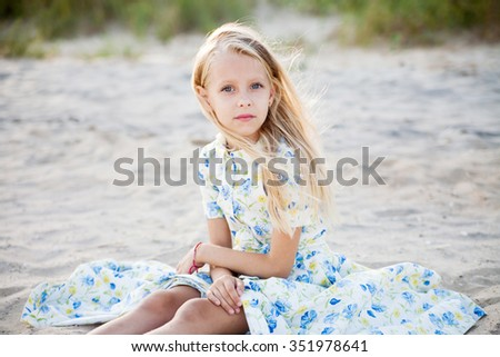 Portrait of a beautiful blonde little girl sitting on the beach at a tropical resort. The concept of rest. Beautiful vintage dress with blue and green flowers. - stock photo