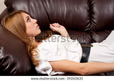 Portrait of a beautiful blonde on a leather couch - stock photo