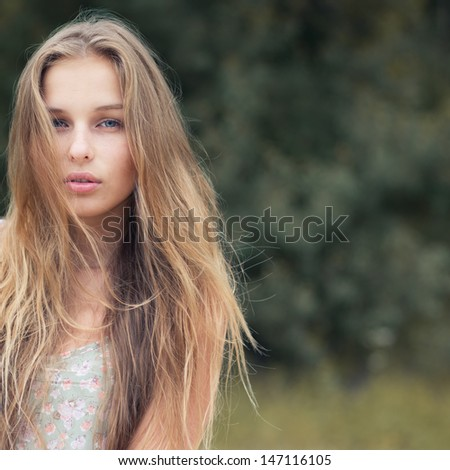 portrait of a beautiful blonde outdoors in the park - stock photo