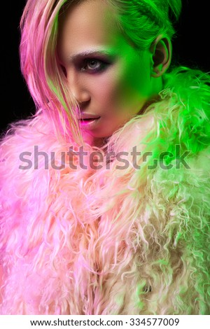 portrait of a beautiful blonde with short hair and green backlighting and pink.