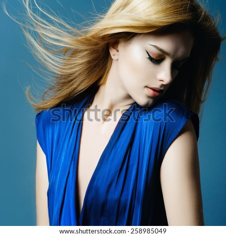 Portrait of a beautiful blonde woman in studio on a blue background with eyes closed, close-up, beauty concept - stock photo