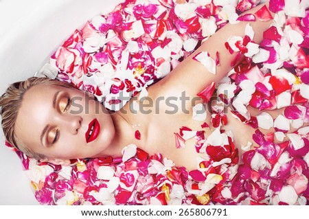 portrait of a beautiful blonde woman in water with rose petal, spa concept, close up portrait - stock photo