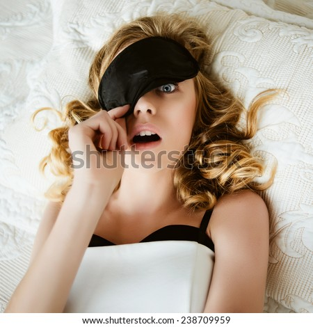 Portrait of a beautiful blonde woman lying on the bed with a mask to sleep, surprise - stock photo