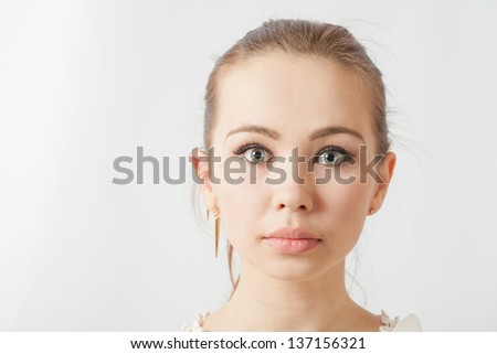 portrait of a beautiful blonde woman with blank expression on white background. - stock photo