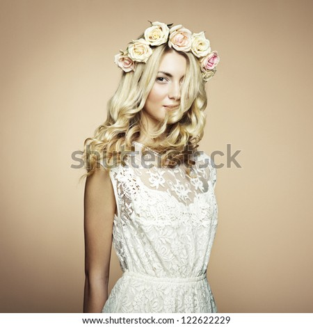 Portrait of a beautiful blonde woman with flowers in her hair. Fashion photo - stock photo