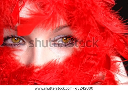 Portrait of a beautiful blonde woman with light green eyes wrapped in red fur boa isolated on white background - stock photo