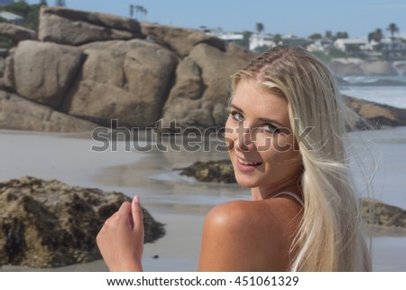 Portrait of a beautiful blonde woman with long hair smiling at the camera with the beach infront of her - stock photo