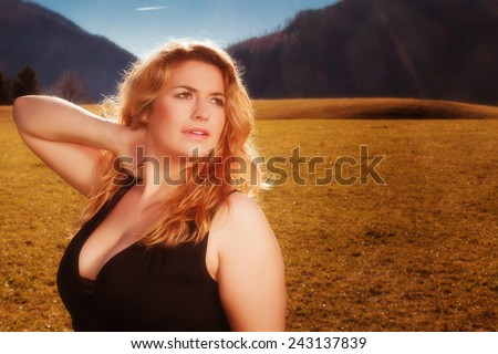 Portrait of a beautiful blonde woman with luscious cleavage in black tank dress. Illuminated on a meadow, the Alps in the background of the autumn sun. / Portrait of a beautiful blonde woman  - stock photo
