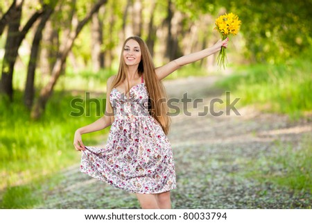 portrait of a beautiful blonde woman with yellow flowers outdoor - stock photo