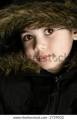 Portrait of a beautiful boy in his fluffy hooded winter coat.