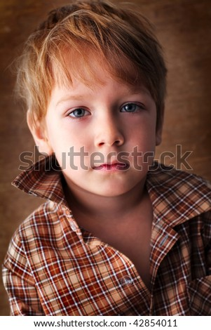 portrait of a beautiful boy on a brown background - stock photo