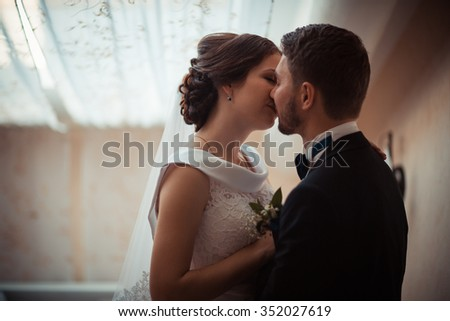 Portrait of a beautiful bride and groom in the marital bedroom - stock photo