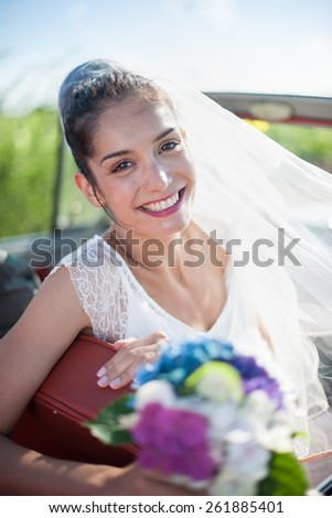 Portrait of a beautiful bride holding her bouquet in a retro car.  Focus on the face