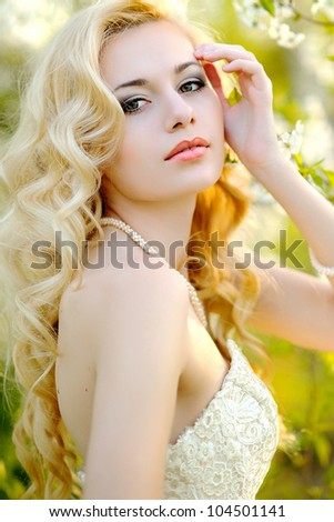 portrait of a beautiful bride in a lush garden - stock photo