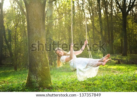 Portrait of a beautiful bride in white wedding dress smiling and swinging in the forest - stock photo