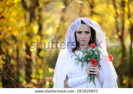 Portrait of a beautiful bride with poppy outdoor
