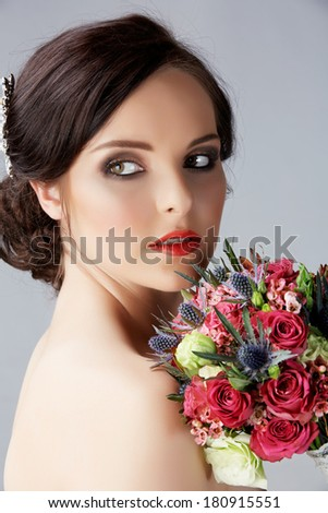 Portrait of a beautiful brunette bride with pink roses bouquet. Hair in romantic hairstyle.  - stock photo