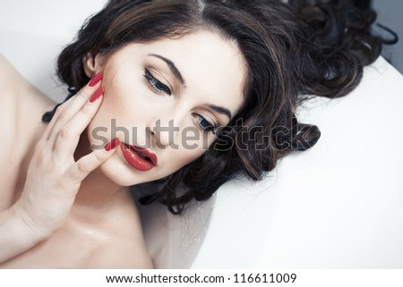 portrait of a beautiful brunette close-up with red lips and red lacquer on the nails