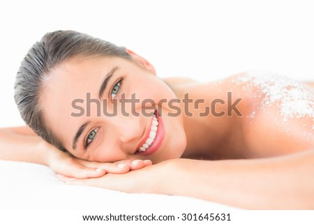 Portrait of a beautiful brunette enjoying a salt scrub treatment at the health spa - stock photo