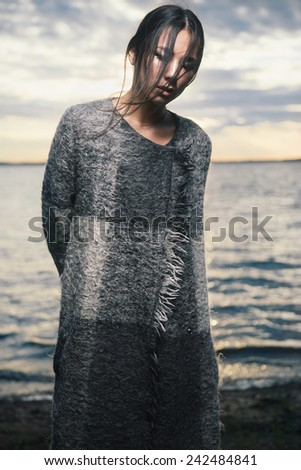 Portrait of a beautiful brunette girl in a coat on a background of the sea at sunset
