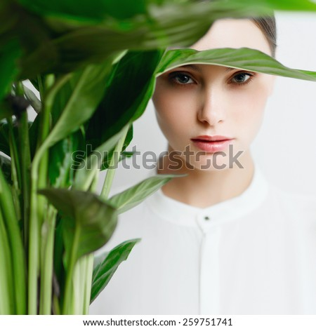 Portrait of a beautiful brunette girl in a white shirt with a green flower in studio - stock photo