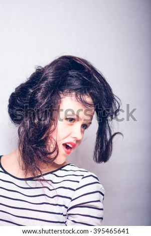 Portrait of a beautiful brunette girl makes a hairstyle isolated on background. Fashion style photo.
