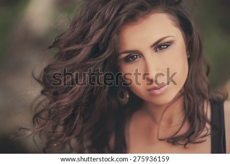 Portrait of a beautiful brunette girl on the nature - stock photo