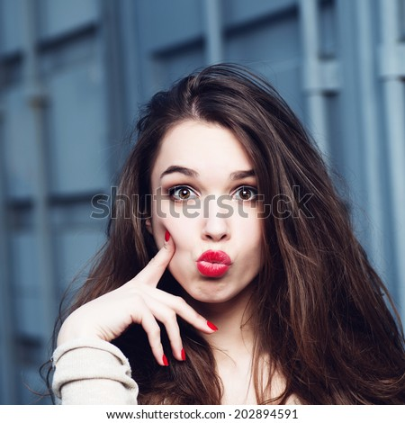 Portrait of a beautiful brunette girl with a surprised look - stock photo