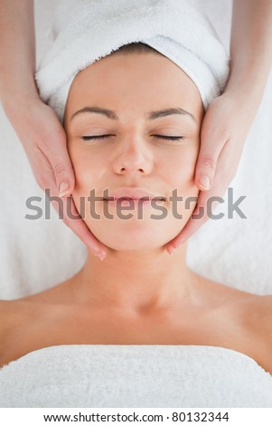 Portrait of a beautiful brunette having a facial massage in a spa - stock photo