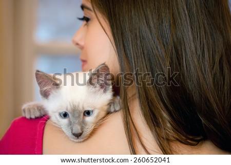 Portrait of a beautiful brunette holding a cute kitten. - stock photo