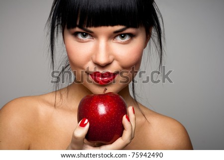 Portrait of a beautiful brunette holding a red apple in hand - stock photo