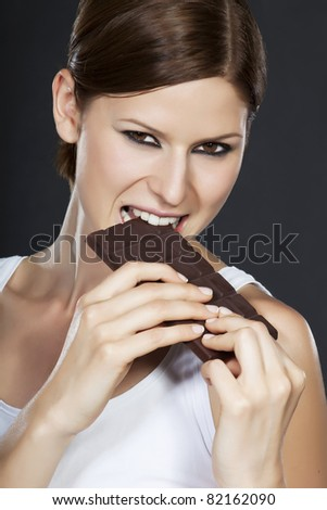 Portrait of a beautiful brunette holding and biting a chocolate bar