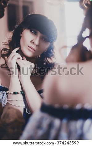 portrait of a beautiful brunette in a blue historic, vintage dress of the 19th century, looking at himself in the mirror