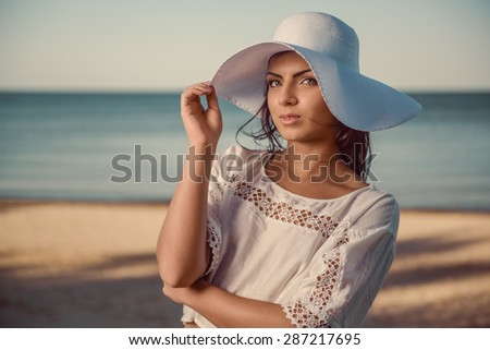 Portrait of a beautiful brunette in white hat - stock photo