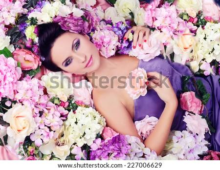 Portrait of a beautiful brunette is relaxing in flower petals. Studio shot. - stock photo