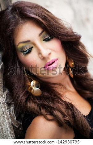 portrait of a beautiful brunette model with long curly hair resting her head against a wall and looking down over her shoulder showing off her tiger looking make-up