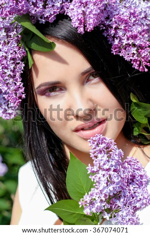 Portrait of a beautiful brunette near the lilacs. Beautiful woman with a wreath on the head of a lilac. Spring. A woman in a spring garden.